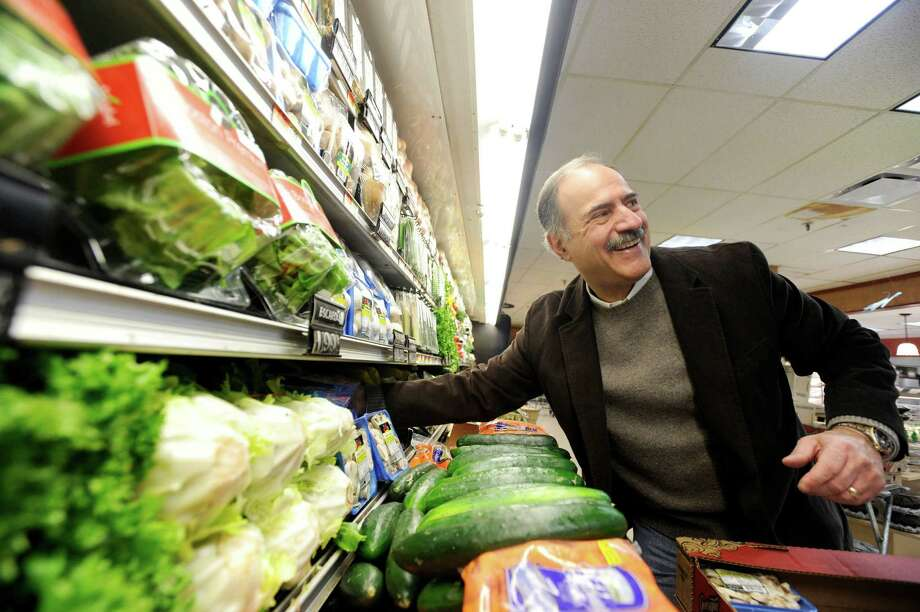 Jerry Porricelli works on the produce layout in the Porricelli's Market in Old Greenwich in this file photo. The Greenwich Chamber of Commerce on Tuesday presented Porricelli with a corporate leader award at its annual award luncheon at the Milbrook Club. Photo: File Photo, ST / Greenwich Time File Photo