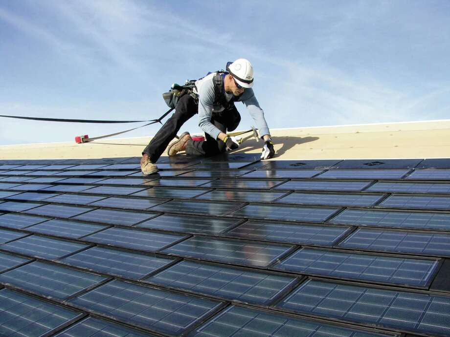 A roofer installs Dow Powerhouse Solar Shingles on a house. The technology combines a roofing shingle with a solar cell. When hooked up to an inverter, the shingles generate power to help offset the homeÕs energy costs. Photo: Courtesy Photo
