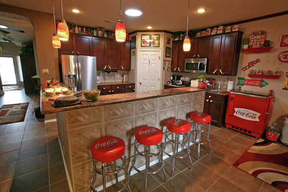 Coca-Cola memorabilia decorates the kitchen; four barstools offer seating at the L-shaped granite bar; the husband refurbished the metal cooler next to the cabinet; itÕs used for storage since it lacks a compressor. Photo: Danny Warner