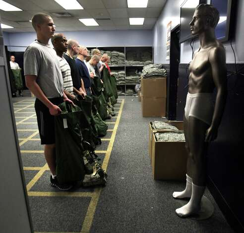 A manikin, right, shows what trainees need to strip down to before they enter a 3-D Body Scanner to determine clothes sizes. The first 72 hours of basic training at Lackland AFB is called Zero Week, when trainees learn to march and speak the Air Force way of life. Thursday, April 19, 2012.  Bob Owen/San Antonio Express-News. Photo: BOB OWEN, San Antonio Express-News / © 2012 San Antonio Express-News