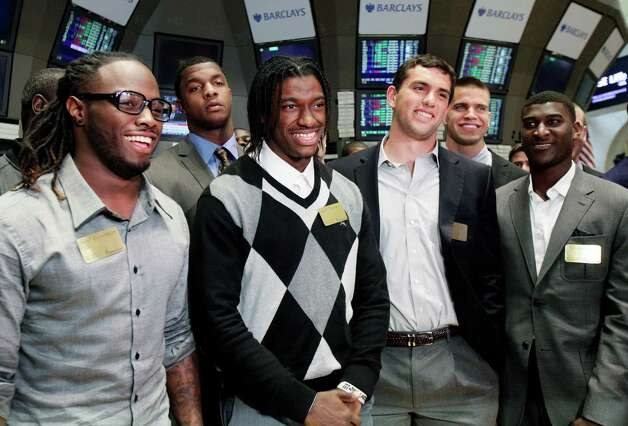 From left, NFL football draft prospects Trent Richardson, of Alabama, Robert Griffin III, of Baylor, Andrew Luck, of Stanford, and Justin Blackmon, of Oklahoma State, pose for photos during their visit to the trading floor of the New York Stock Exchange, Wednesday, April 25, 2012. The college stars are preparing for the NFL draft Thursday night at Radio City Music Hall. Photo: AP