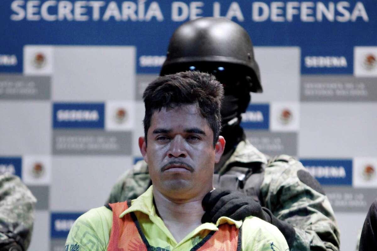 A soldier escorts Julian Zapata Espinosa, aka