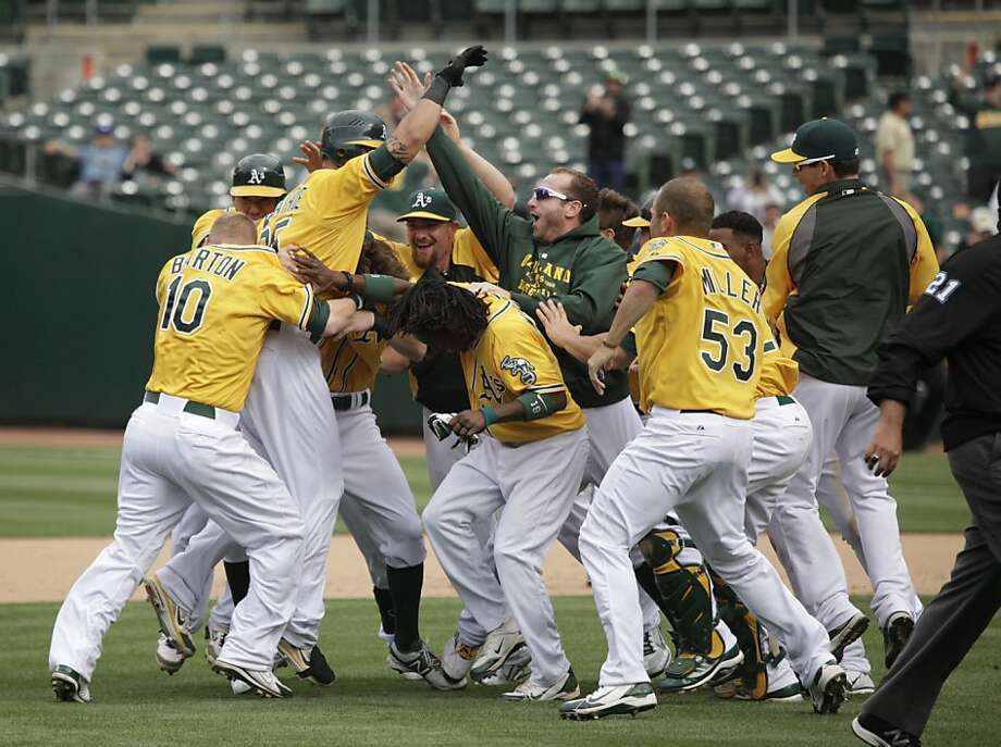 A's players mob Kila Ka'aihue, whose 14th-inning single finished off the White Sox. Photo: Lea Suzuki, The Chronicle