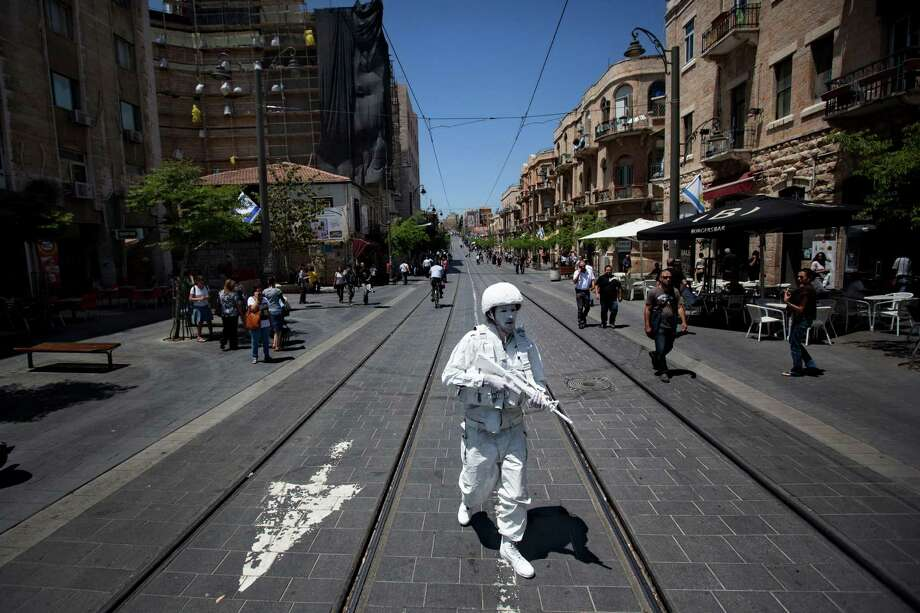 "Artist Matan Goldberg, walks in Jerusalem as a part of performance titled ""The White Soldier"" , Wednesday, April 25, 2012. On Wednesday Israel marks Memorial Day in remembrance of the nation's fallen soldiers since 1948.  Artists symbolically patrolled along the 1967 'Green Line' which separated Israel from the Jordanian-controlled East Jerusalem which was captured by Israel in the 1967 Six-Day-War. Photo: Oded Balilty, Associated Press / AP"