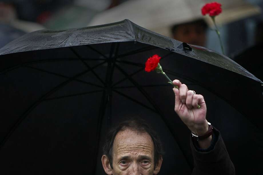 TOPSHOTS A man holds a red carnation, a symbol of the 1974 Portuguese revolution, as he march in downtown Lisbon on April 25, 2012, during a demonstration to celebrate the 38th anniversary of the revolution day in Portugal. TOPSHOTS/AFP PHOTO/ PATRICIA DE MELO MOREIRAPATRICIA DE MELO MOREIRA/AFP/GettyImages Photo: Patricia De Melo Moreira, AFP/Getty Images