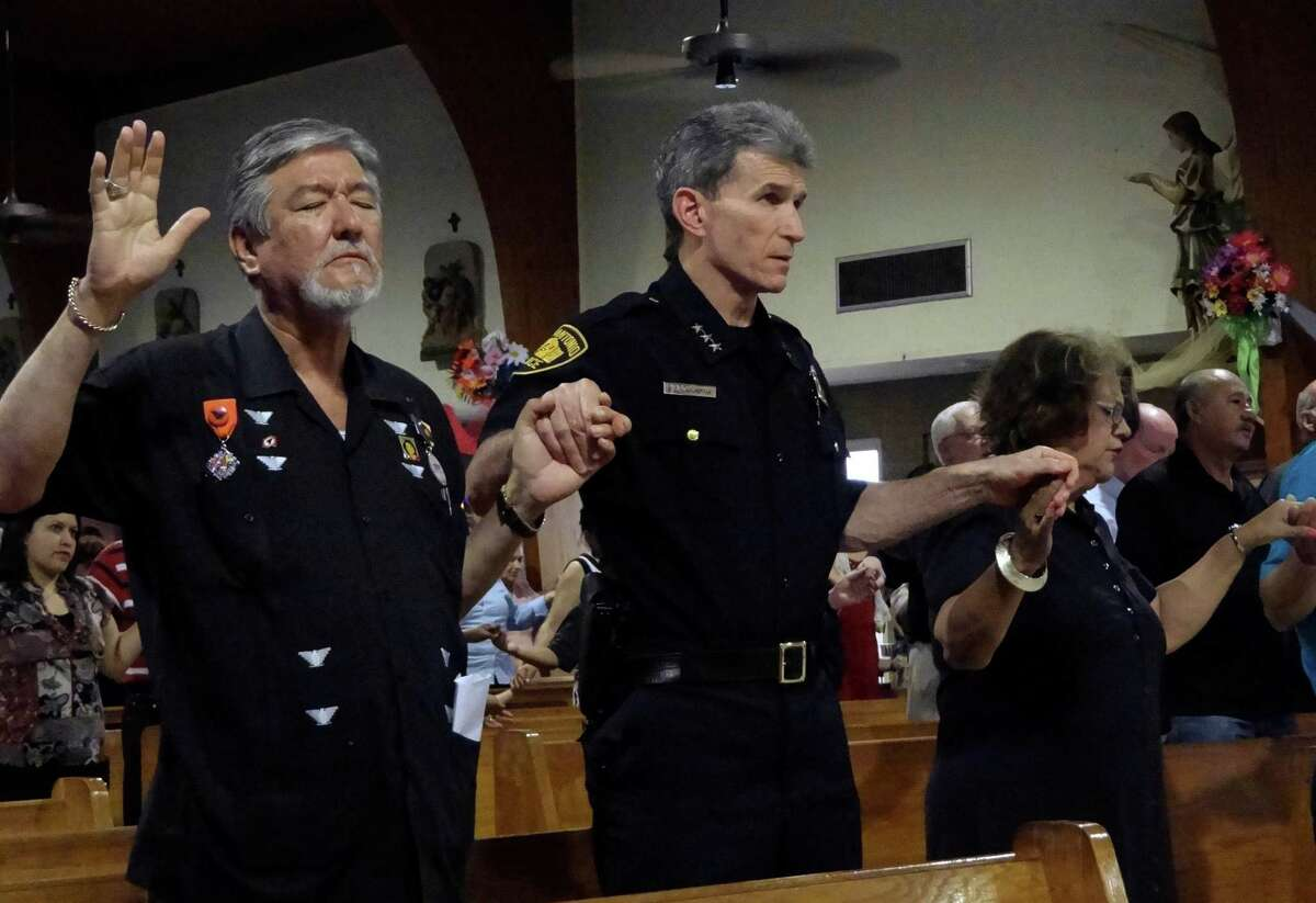 """San Antonio Police Chief William McManus, middle, participates in a """"Mass for Justice"""" at Sacred Heart Catholic Church on Wednesday, April 25, 2012. Jaime P. Martinez, left, is the founder of the Cesar E. Chavez Foundation. The service was said to address the Arizona anti-immigration law, S.B. 1070, which was heard by the United States Supreme Court. McManus said that the San Antonio police do not care about a person's immigration status. Billy Calzada / San Antonio Express-News"""