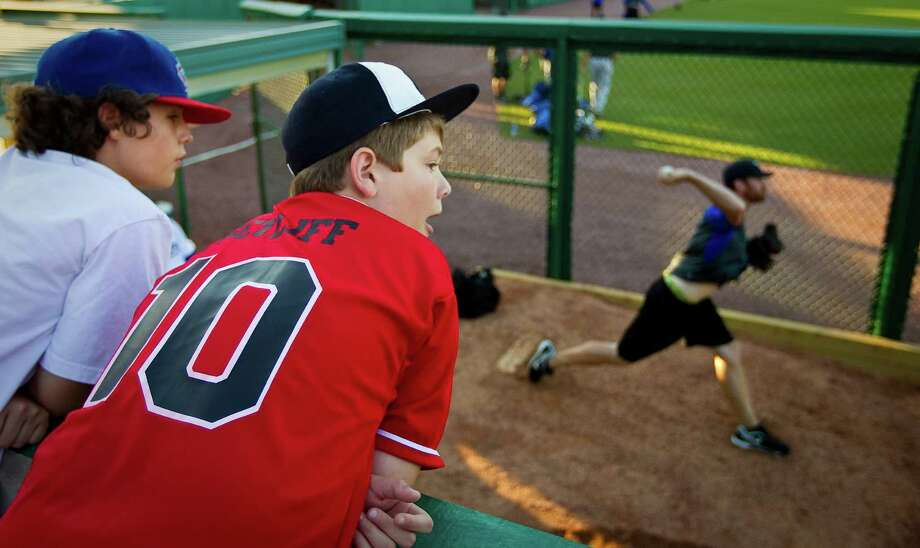 Drew Decker, left, and his friend Brandon Setliff, both 12, lean in for a peek at the Skeeters pitching staff at Constellation Field. Photo: Nick De La Torre / © 2012  Houston Chronicle
