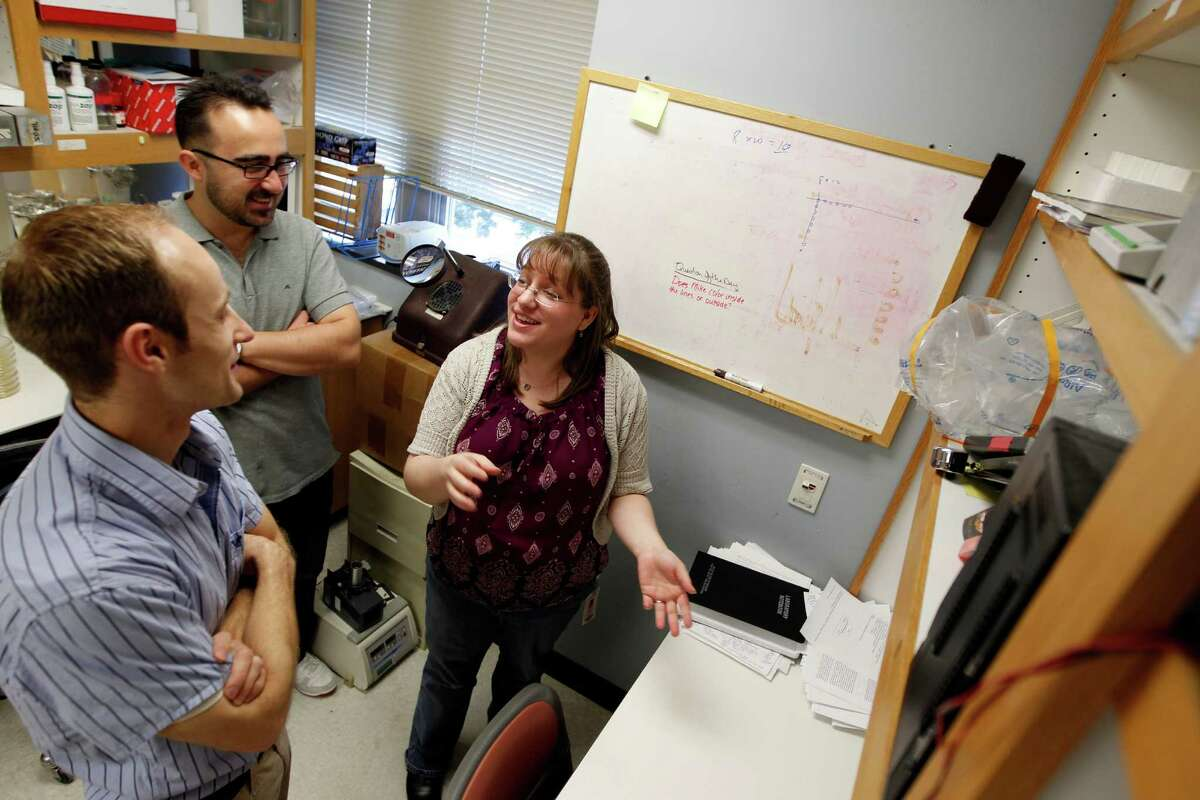 """Students Truston Bodine, left, Vlatko Stojanoski, center, and Kim Carlson prepare for a weekly department meeting at Baylor College of Medicine. """"If you want to do bad science, you work alone,"""" Carlson says."""