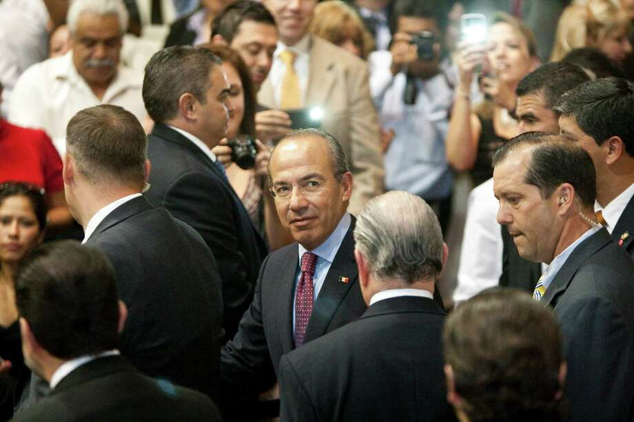 Mexican President Felipe Calderon, facing, shakes hands as he walks to his seat, Wednesday, April 25, 2012, in the Ripley House community center gymnasium in Houston. Photo: Nick De La Torre, Houston Chronicle / © 2012  Houston Chronicle