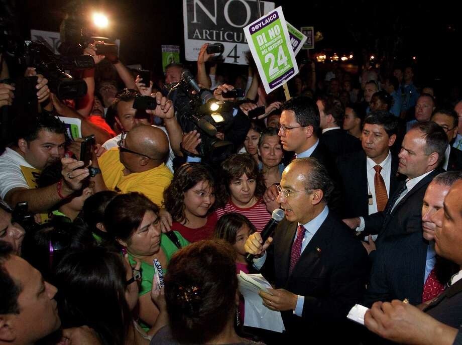 Mexican President Felipe Calderon, center, address a crowd that gathered to protest the possible changes to in article 24 of the Mexican constitution, Wednesday, April 25, 2012, outside the Ripley House community center in Houston. Photo: Nick De La Torre, Houston Chronicle / © 2012  Houston Chronicle