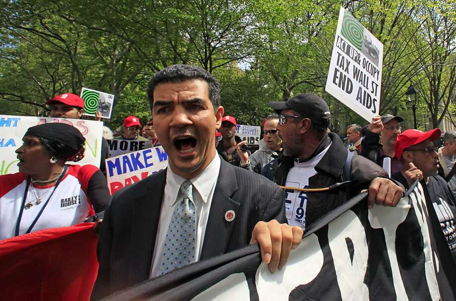 New York City Councilman Ydanis Rodriguez, center, chants as he joins a rally and demonstration march around the Wall Street financial district to commemorate AIDS Coalition To Unleash Power (ACT UP) on Wednesday, April 25, 2012 in New York. (AP Photo/Bebeto Matthews) Photo: Bebeto Matthews, Associated Press