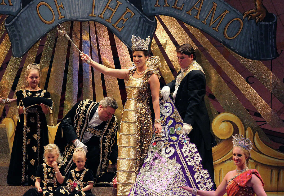 Kahler Elizabeth Biedenharn (center) waves the royal sceptre after being crowned as Queen of The Wondrous Metropolis by President of the Order of the Alamo, Stanton Paul Bell (left of Biedenharn) at the 2012 Coronation of the Order of the Alamo at the Majestic Theater on Wednesday, Apr. 25, 2012.