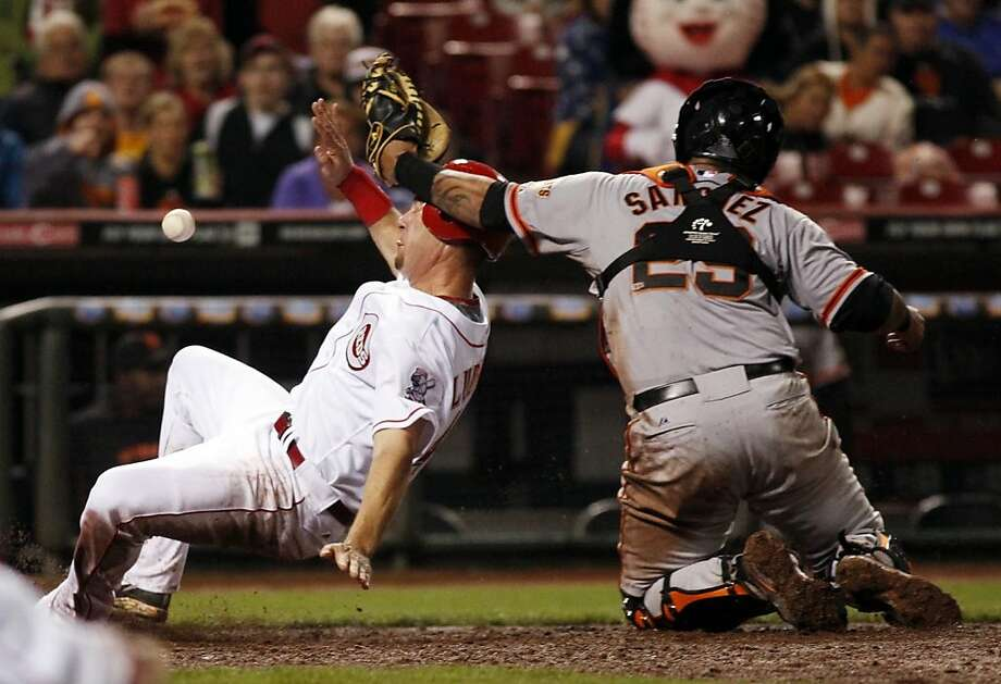 Cincinnati Reds Ryan Ludwick, left, slides safely into home in the seventh inning of a baseball game against the San Francisco Giants, Wednesday, April 25, 2012, in Cincinnati. Giants catcher Hector Sanchez is unsuccessful with the tag. (AP Photo/Ernest Coleman) Photo: Ernest Coleman, Associated Press