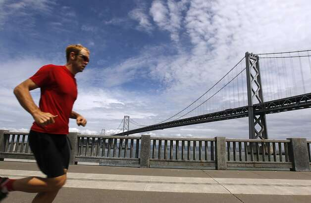 A jogger runs past the Bay Bridge on The Embarcadero in San Francisco, Calif. on Wednesday, April 25, 2012. The San Francisco metropolitan area has dropped off the list of the top 25 most polluted regions in the nation, according to the American Lung Association's annual report on air quality and four of the nine cleanest counties in the state are in the Bay Area. Photo: Paul Chinn, The Chronicle