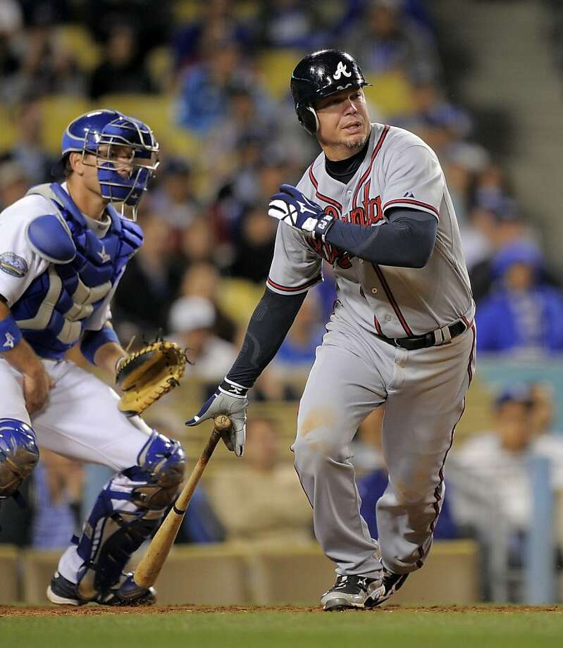 Atlanta Braves' Chipper Jones, rihgt, hits an RBI single as Los Angeles Dodgers catcher A.J. Ellis looks on during the ninth inning of their baseball game, Wednesday, April 25, 2012, in Los Angeles. (AP Photo/Mark J. Terrill) Photo: Mark J. Terrill, Associated Press