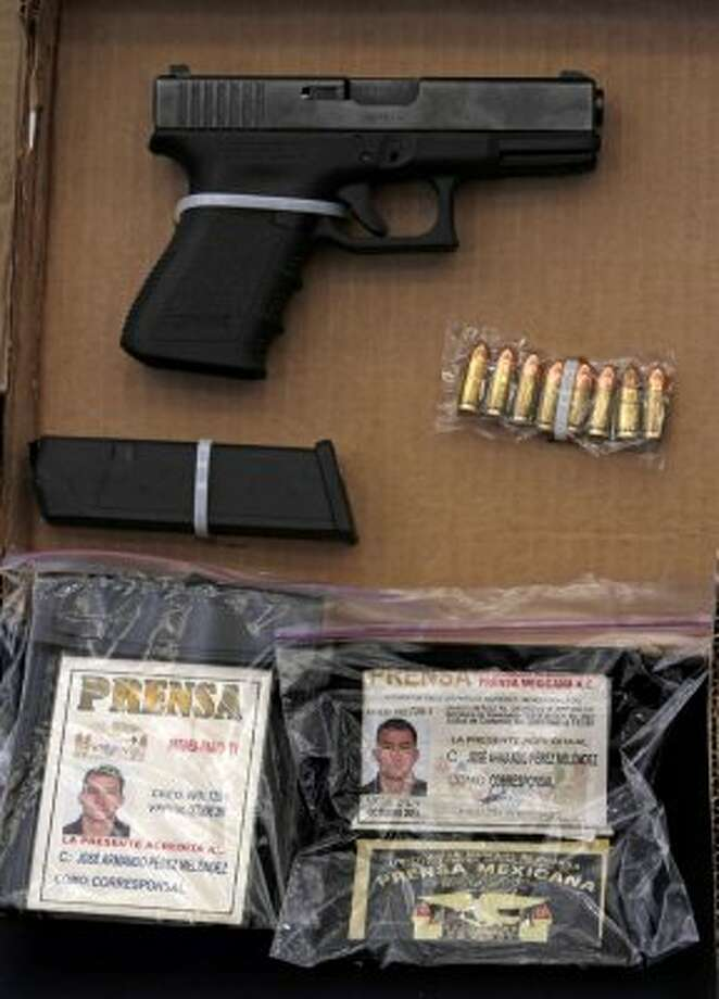 "A gun and press credentials seized Saturday in Mexico City. Mexican authorities said they belonged to Jose Antonio Torres Marrufo. He is the suspected leader of ""Gente Nueva,""an armed wing of the Sinaloa Cartel. (Associated Press)"