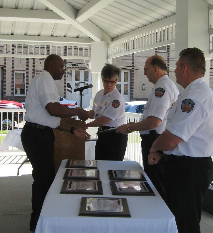 District Chief Keith Stewart accepts a plaque and shakes hands with Capt. Brad Penisson on Wednesday during a ceremony honoring the Beaumont Fire Department personnel who responded to the March 14 courthouse shooting. Photo: Sarah Moore
