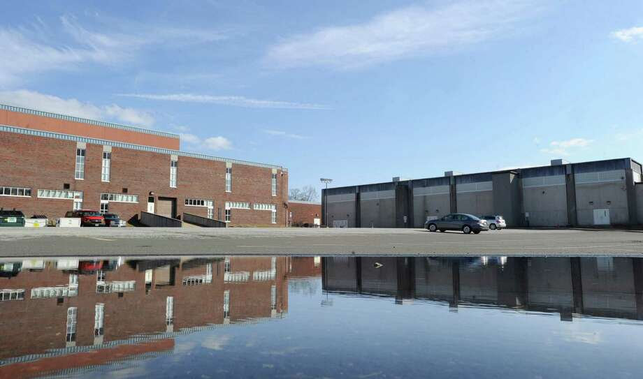 Greenwich High School as seen reflected in a puddle in the western parking lot Feb. 17, 2012. Toxins discovered in the soil on school property during 2011 have stalled the school's auditorium project. Photo: Bob Luckey / Greenwich Time