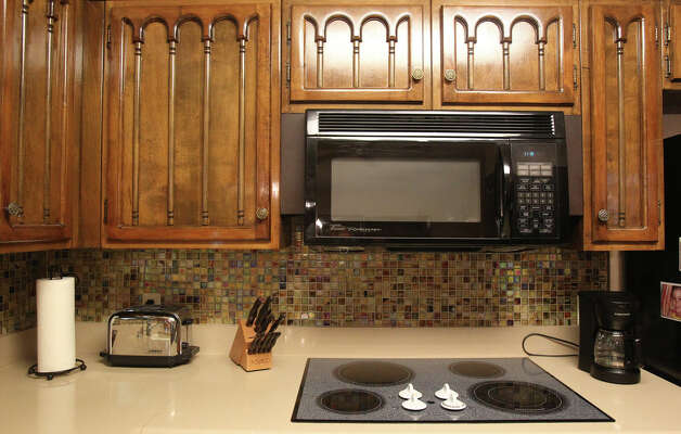 A built in microwave oven and a cook top flush with the counter top are focal points in the kitchen of Rose Mary Zepeda. Rich wood cabinetry is throughout the kitchen. (Friday April 20, 2012) John Davenport/San Antonio Express-news Photo: JOHN DAVENPORT, SAN ANTONIO EXPRESS-NEWS / SAN ANTONIO EXPRESS-NEWS (Photo can be sold to the public)