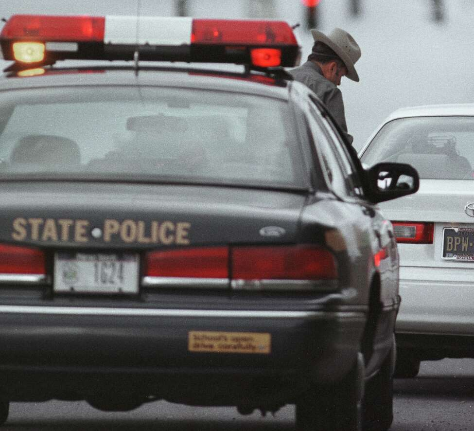 FILE - Trooper Mike Anson prepares to issue a traffic summons to a driver on Oct. 29, 1998, on Interstate 87 during a blanket patrol for aggressive driving.
