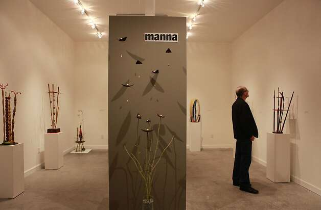 A patron studies a Manna Gallery piece. Patrons see the art walk as a way to support emerging artists. Photo: Jill Schneider, The Chronicle