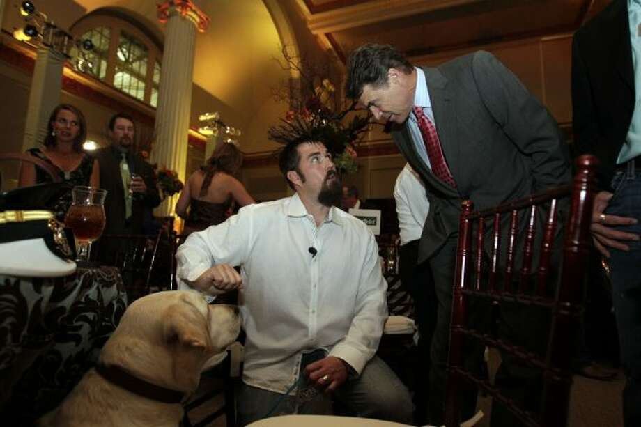 Gov. Rick Perry talks with retired U.S. Navy SEAL Marcus Luttrell next to Luttrell's dog Rigby before Perry spoke to an audience of more than 200 during the Lone Survivor Foundation's 2011 Second Annual Gala titled Mission: Never Quit at Minute Maid Park Saturday, Sept. 17, 2011, in Houston.  Featured speakers included Perry, Luttrell and retired U.S. Army Ranger Capt. Chad Fleming. The Lone Survivor Foundation was established in 2010 by Luttrell in an effort to give back to those that have served in the U.S. military. (Johnny Hanson / Houston Chronicle)