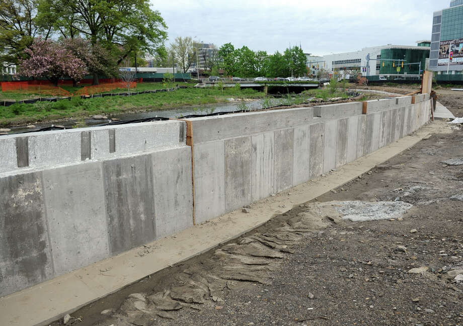 Progress at Mill River Park includes the removal of unsuitable topsoil, compacting of existing soil, the building of a retaining wall near the river, as well as plumbing and electrical systems. Photo: Lindsay Niegelberg / Stamford Advocate