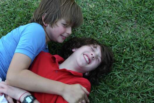 Peter Berry, right, 10, wrestles with his cousin, Noah, 10, during their regular after school ritual of playing in the front yard where they live together Thursday, April 19, 2012, in Houston. Photo: Johnny Hanson, Houston Chronicle / © 2012  Houston Chronicle