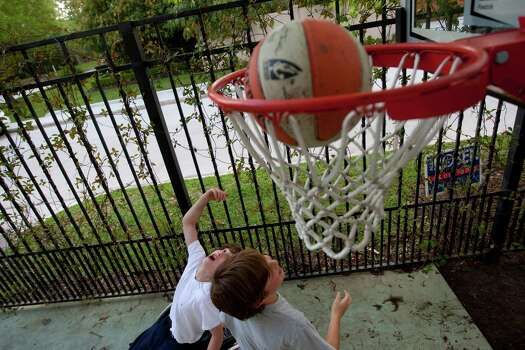 Peter Berry, 10, hooks a shot into the basket while playing with his cousin, Noah, 10. Photo: Johnny Hanson, Houston Chronicle / © 2012  Houston Chronicle