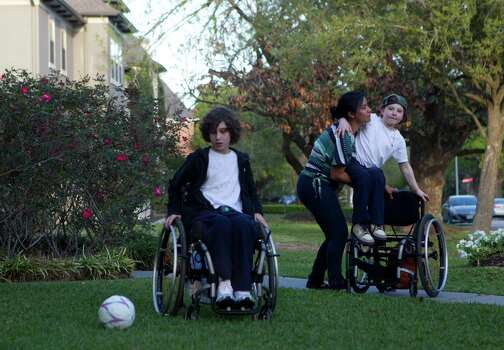 Wendy Ortiz, who has been Aaron and Peter's caretaker since Aaron was 8 months old, lifts Aaron, 9, out of his wheelchair so he could play ball with his brother Peter, 10, left, and his cousins in the front yard. Photo: Johnny Hanson, Houston Chronicle / © 2012  Houston Chronicle