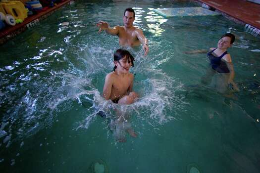 Taking a break from therapy and having a bit of fun, Peter does a cannonball with the help of therapist Jon Hartzel as therapist Hayden Sanford looks on. Photo: Johnny Hanson, Houston Chronicle / © 2012  Houston Chronicle