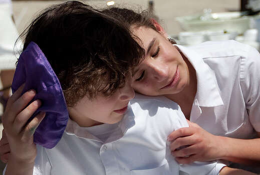 Peter Berry, 10, hugged by longtime friend Lila Deutsch, 11, during lunch at the Beth Yeshurun Day School .
