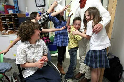 Next to Peter Berry, 10, girls surround one of the more than a dozen University of Texas Cowboys that came to visit Peter, his brother and sister as part of a service project the group is doing to raise money for the family at Beth Yeshurun Day School Thursday, April 5, 2012, in Houston.  Photo: Johnny Hanson, Houston Chronicle / © 2012  Houston Chronicle