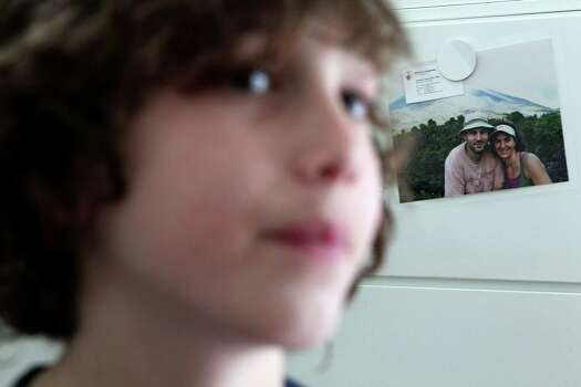 Peter concentrates on playing a video game next to a picture of his mother and father, Joshua and Robin, he has hanging in his room. Photo: Johnny Hanson, Houston Chronicle / © 2012  Houston Chronicle