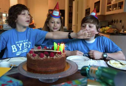 "Next to his sister Willa, 6, center, Peter, 10, left, stops Aaron from blowing out the last candle, telling him to make sure he wishes for  ""something you really want to happen,"" as  they celebrated Aaron's 9th birthday before school in Bellaire. Photo: Johnny Hanson, Houston Chronicle / © 2012  Houston Chronicle"