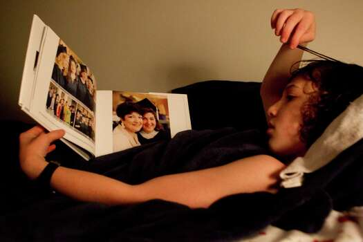 Peter Berry, 10, looks at a book of pictures of his mother, Robin, before he went to bed Monday, March 12, 2012, in Bellaire. 