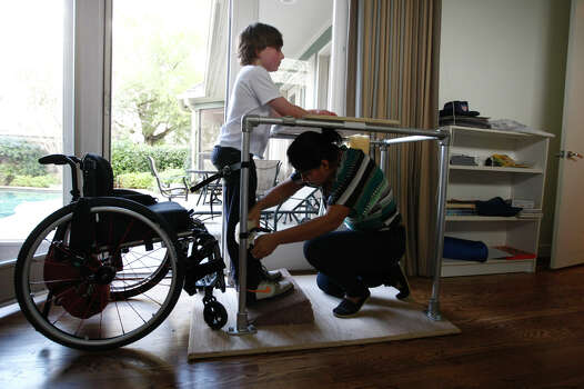 Wendy Ortiz, who has been Aaron's nanny since he was 8 months old, straps him into a standing position, one of the daily rituals of Aaron and Peter's recovery process. Photo: Johnny Hanson, Houston Chronicle / © 2012  Houston Chronicle