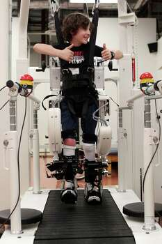 Peter Berry, 10, gives a thumbs up while performing an assisted walking exercise to aid in neuromuscular re-education at TIRR. Photo: Johnny Hanson, Houston Chronicle / © 2012  Houston Chronicle