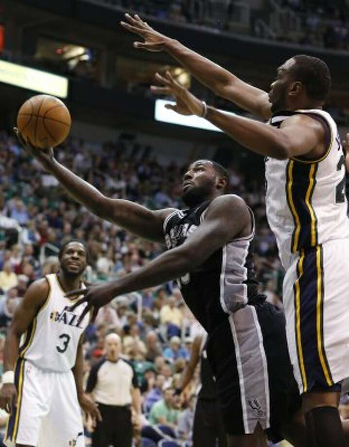 Spurs forward DeJuan Blair, left, takes a shot while defended by Jazz center Al Jefferson during the first half of a game Monday, April 9, 2012, in Salt Lake City. (AP Photo/Jim Urquhart) (AP)