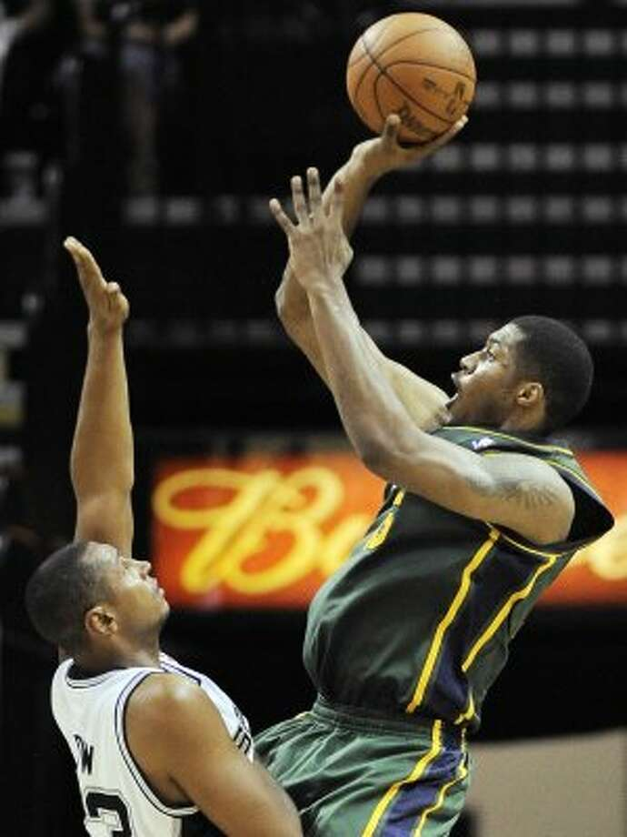 The Jazz's Derrick Favors, right, shoots over the Spurs' Boris Diaw during the second half of a game, Sunday, April 8, 2012, in San Antonio. San Antonio won 114-104. Express-News writer Jeff McDonald expects to see more of Tiago Splitter and Boris Diaw in the playoff series, as the Spurs attempt to match size. (AP Photo/Darren Abate) (AP)