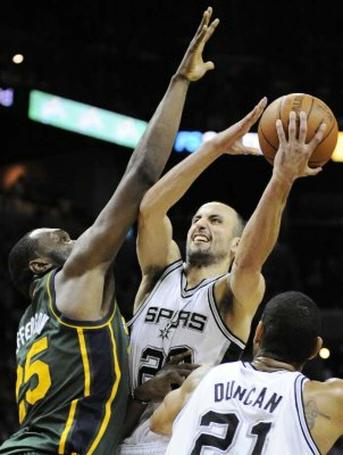 The Spurs' Manu Ginobili, center, shoots over the Jazz's Al Jefferson during the second half of a game, Sunday, April 8, 2012, in San Antonio. San Antonio won 114-104. (AP Photo/Darren Abate) (AP)