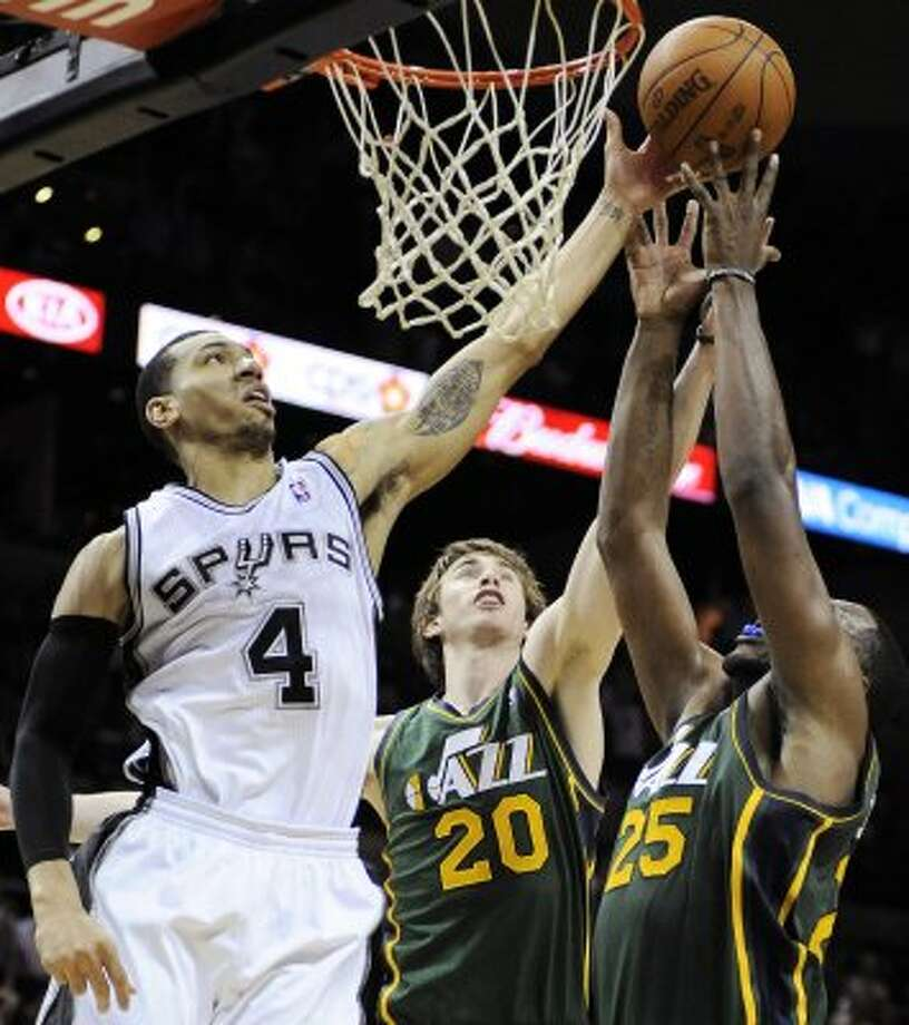 The Spurs' Danny Green (4) shoots over the Jazz's Gordon Hayward (20) and Al Jefferson during the second half of a game, Sunday, April 8, 2012, in San Antonio. San Antonio won 114-104. (AP Photo/Darren Abate) (AP)