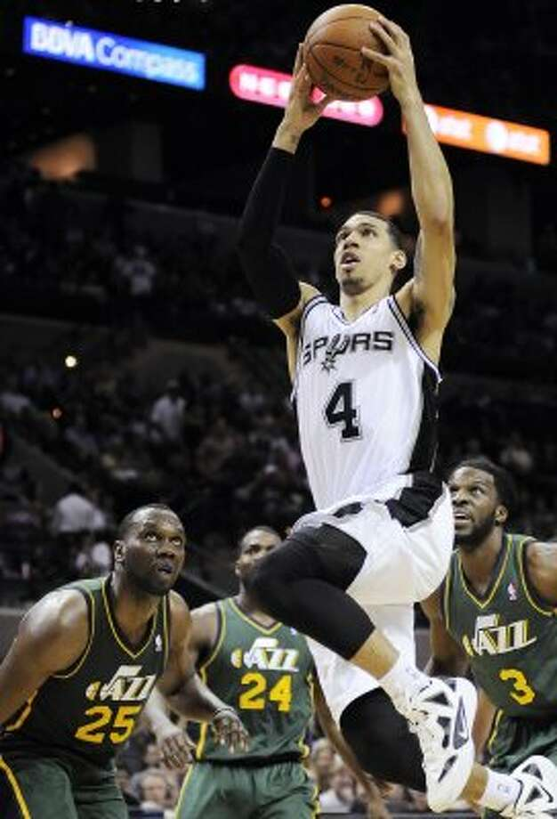 The Spurs' Danny Green (4) shoots ahead of the Jazz's Al Jefferson (25), Paul Millsap (24) and DeMarre Carroll (3) during the second half of a game, Sunday, April 8, 2012, in San Antonio. (AP Photo/Darren Abate) (AP)