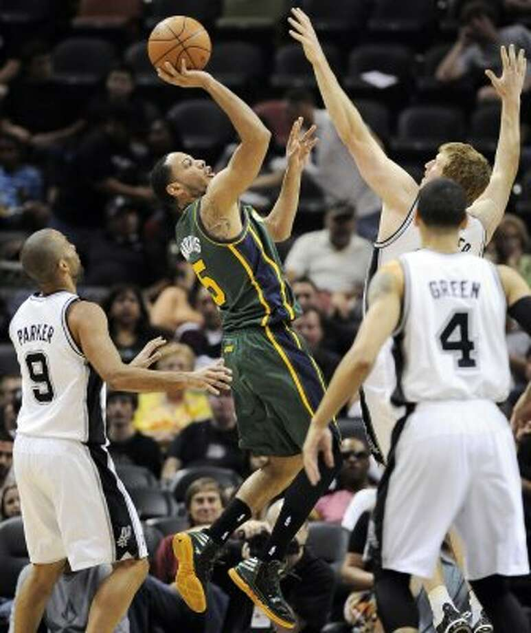 The Jazz's Devin Harris, center, shoots between the Spurs' Tony Parker (9), Danny Green (4) and Matt Bonner during the second half of a game, Sunday, April 8, 2012, in San Antonio. (AP Photo/Darren Abate) (AP)