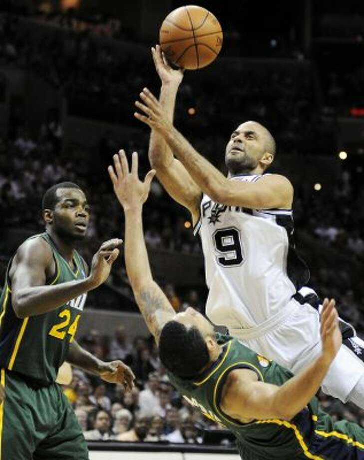The Spurs' Tony Parker (9), shoots over the Jazz's Devin Harris and Paul Millsap (24) during the second half of a game, Sunday, April 8, 2012, in San Antonio. (AP Photo/Darren Abate) (AP)