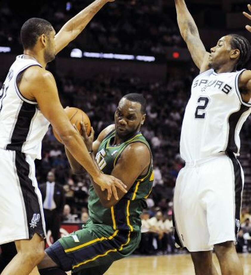 The Jazz's Al Jefferson, center, is defended by the Spurs' Tim Duncan, left, and Kawhi Leonard during the first half of a game, Sunday, April 8, 2012, in San Antonio. (AP Photo/Darren Abate) (AP)