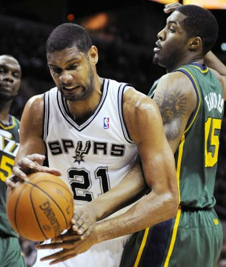 The Spurs' Tim Duncan (21) fights for a rebound with the Jazz's Derrick Favors during the first half of a game, Sunday, April 8, 2012, in San Antonio. Utah is the NBA's third-best rebounding team, behind only Chicago and the L.A. Lakers. Off and on, rebounding has been problematic for the Spurs at times this year. (AP Photo/Darren Abate) (AP)