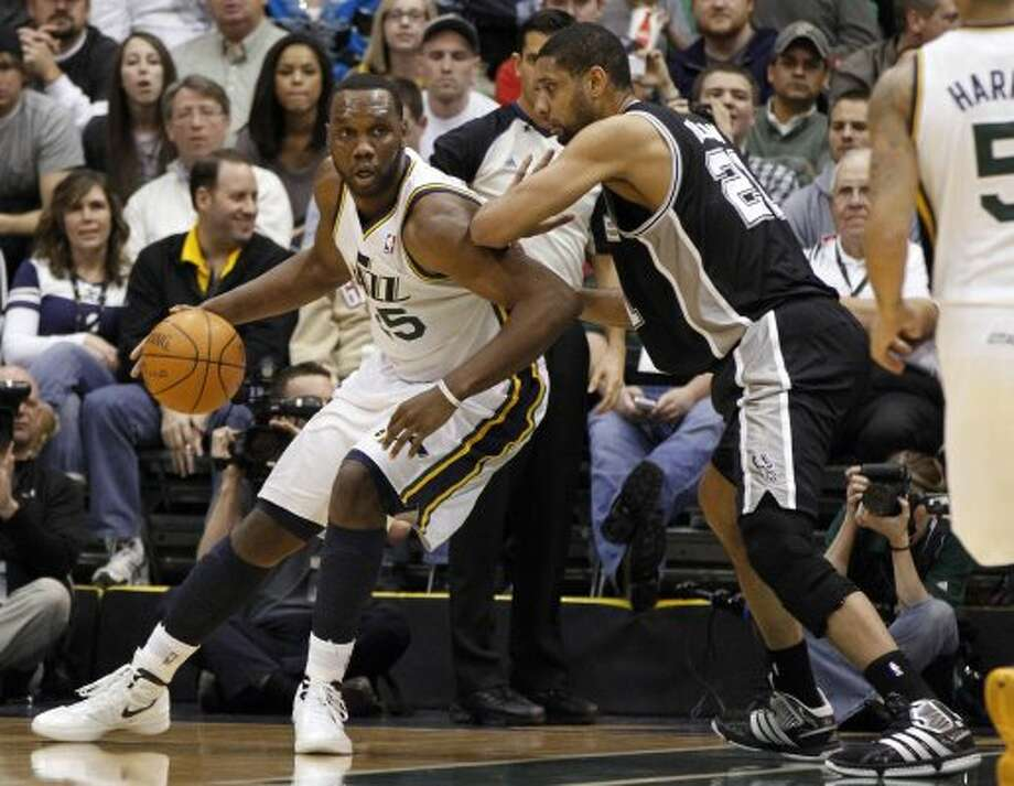 Jazz center Al Jefferson, left, is defended by Spurs forward Tim Duncan (21) during the first half of a game Monday, Feb. 20, 2012, in Salt Lake City. (AP Photo/Jim Urquhart) (AP)