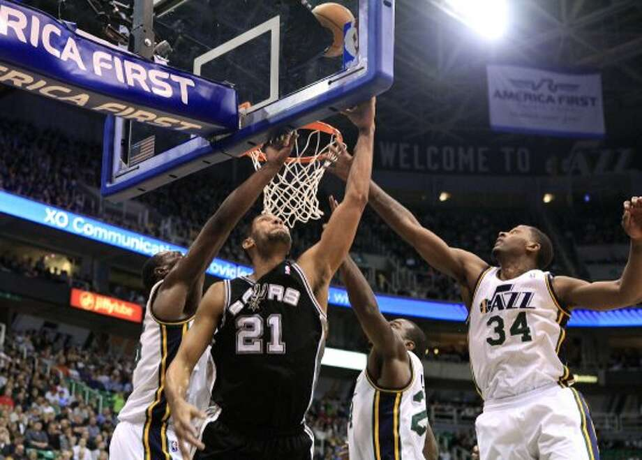 Spurs forward Tim Duncan (21) attempts a shot while defended by Jazz center Al Jefferson, left, forwards Paul Millsap, second from right, and C.J. Miles (34) during the first half of a game, Monday, Feb. 20, 2012, in Salt Lake City. (AP Photo/Jim Urquhart) (AP)