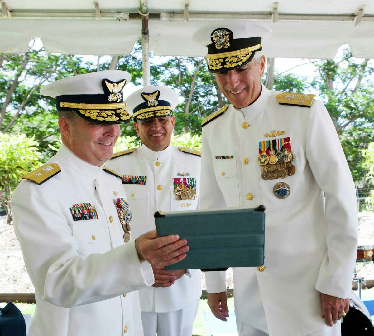 Rear Adm. Christopher Tomney of the U.S. Coast Guard (left) holds an iPad as both Adm. Samuel J. Locklear, commander, U.S. Pacific Command, (right) and new Rear Adm. Jim Rendon (center) chat to Tomney's mother.